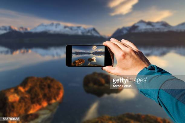 Photographing with smartphone in hand. Travel concept. Norway, sunset over the fjord