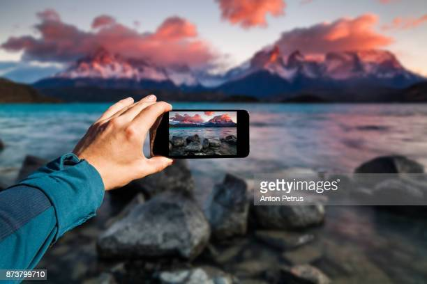 photographing with smartphone in hand. travel concept. torres del paine, chili - photography themes stock pictures, royalty-free photos & images