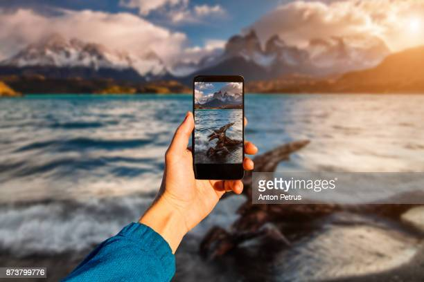 photographing with smartphone in hand. travel concept. torres del paine, chili - temi per la fotografia foto e immagini stock