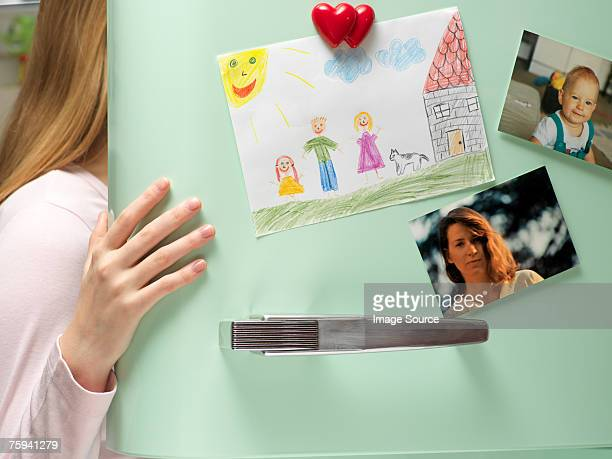 Photographs and drawing on refrigerator door