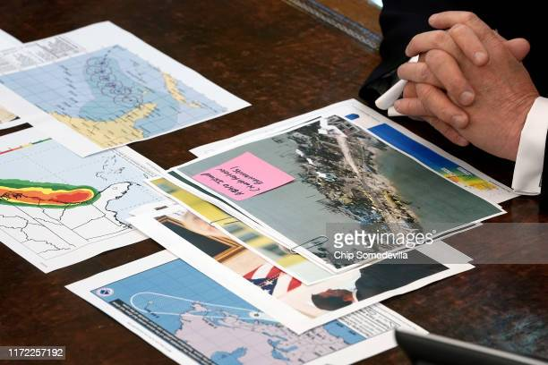 Photographs and maps sit on U.S. President Donald Trump's desk as he talks to reporters following a briefing from officials about Hurricane Dorian in...