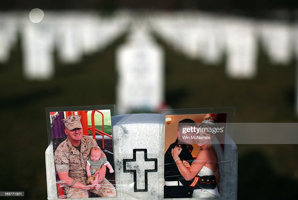 Photographs cover the top of the headstone at the grave of USMC Sgt. Christopher James Jacobs in Section 60 at Arlington National Cemetery March 15, 2013 in Arlington, Virginia. Section 60 is the section of the cemetery where American military members killed in Iraq and Afghanistan are currently laid to rest, though soldiers and Marines from World War II through Afghanistan are also buried in the section. March 20, 2013 marks the ten-year anniversary of the beginning of the war in Iraq.