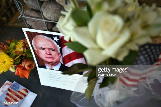 TOPSHOT Photographs flowers and notes gather at a makeshift memorial to US Senator John McCain outside his office in Phoenix Arizona on August 26...