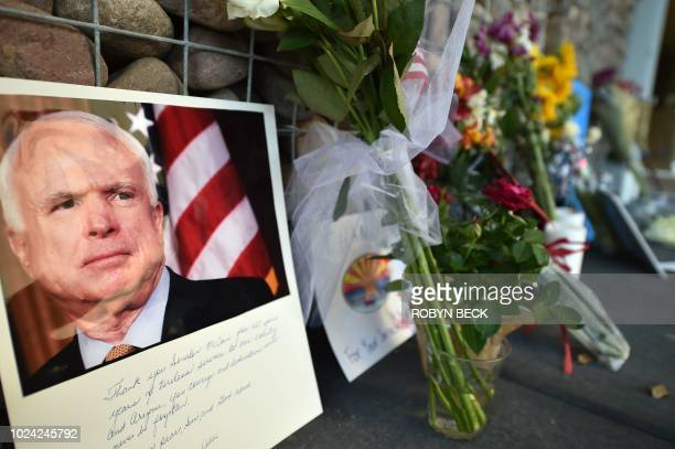 Photographs flowers and notes gather at a makeshift memorial to US Senator John McCain outside his office in Phoenix Arizona on August 26 2018 McCain...