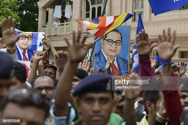 Photographs of Dr Ambedkar are raised as Indian members of the Dalit caste community take a pledge not to skin cattle during a protest rally against...