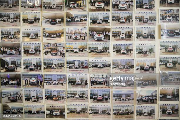 Photographs of employees with owners of new Ford Motor Co vehicles are displayed on a wall at a Ford dealership in Shanghai China on Thursday July 19...