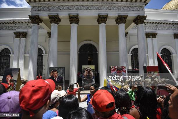 Photographs of late Venezuelan president Hugo Chavez hang on display outside the National Assembly building in Caracas Venezuela on Friday Aug 4 2017...