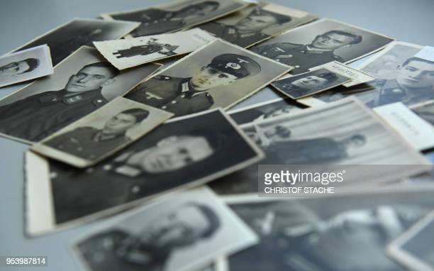 Photographs of missing former German soldiers lie on a table at the German Red Cross archive in Munich southern Germany on April 9 2018 Diethild...