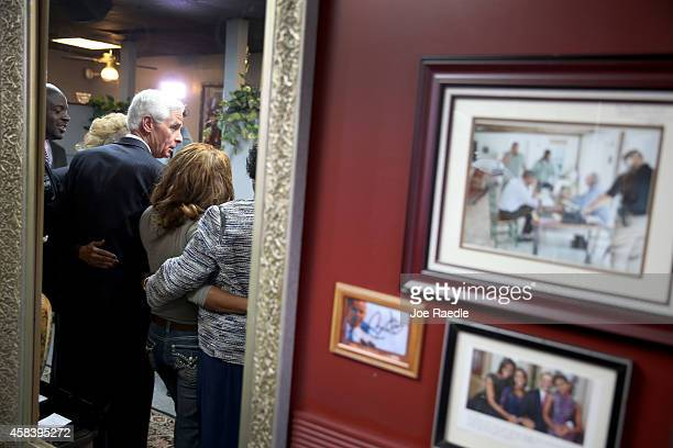 Photographs of President Barack Obama and the First Family are seen hanging on the wall as former Florida Governor and now Democratic gubernatorial...