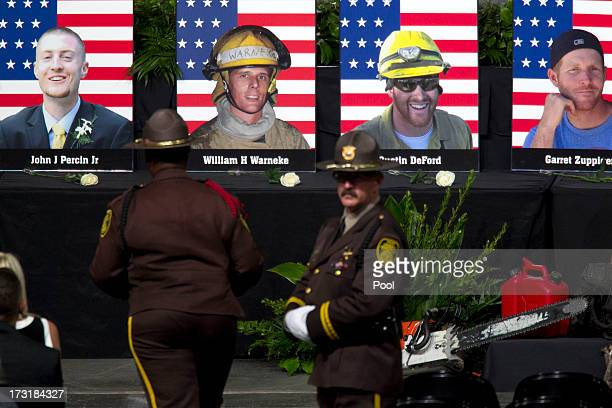 Photographs of the 19 fallen firefighters are seen before the Our Fallen Brother memorial service honoring 19 fallen firefighters at Tim's Toyota...