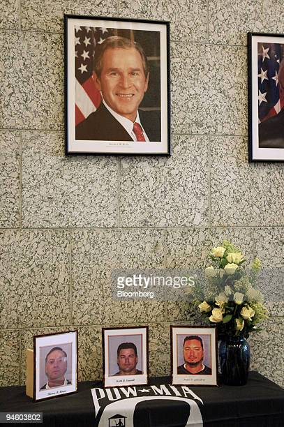 Photographs of three kidnapped Defense Department contractors Thomas Howes left Keith Stansell center and Marc Gonsalves sit on a table covered by a...