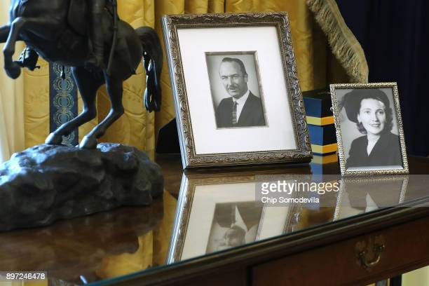 Photographs of US President Donald Trump's parents stand on the table behind his desk as he signs the tax reform bill into law in the Oval Office at...