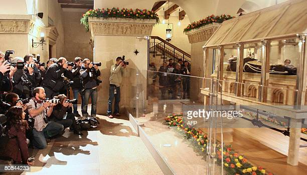 Photographs take pictures of the body of Padre Pio in a partglass coffin in the crypt of the old Church of St Mary of Grace at San Giovanni Rotondo...