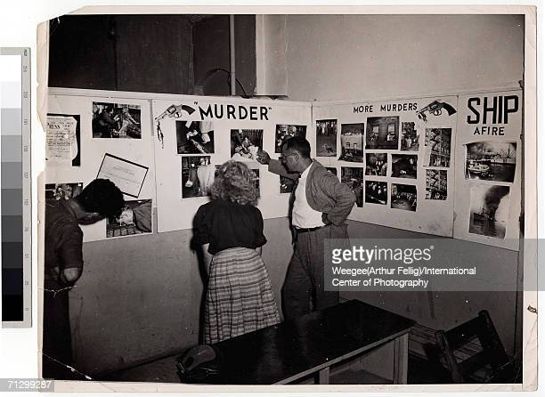 Photography fans examine a series of wall-mounted collages at Weegee's one man exhibition, 'Murder is My Business,' held at the New York Photo...