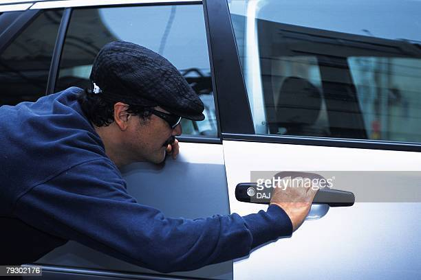 Photography of a burglar breaking into a car, Side View