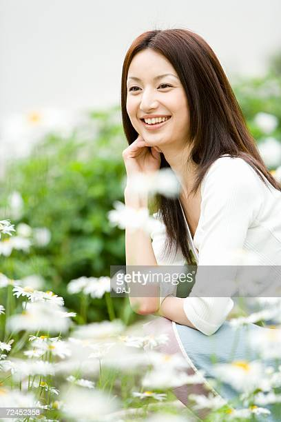 Photography of a mid adult woman surrounded by flowers, Differential Focus