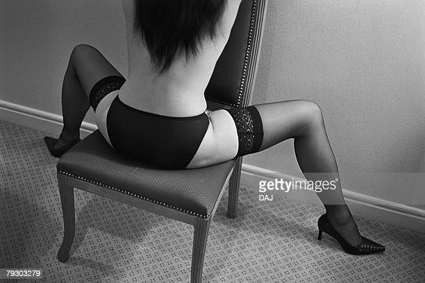 Photography of a woman with lingerie sitting on a chair backwards with legs wide open, Rear View, Black and White