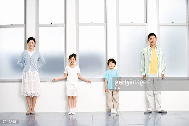 Photography of parents and children standing by the windows, Front View