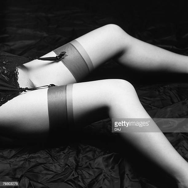photography of womans legs with garter belt lying down, high angle view, black and white - stockings and suspenders - fotografias e filmes do acervo