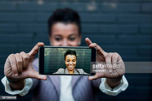 Photography of young woman taking a selfie on display of smartphone