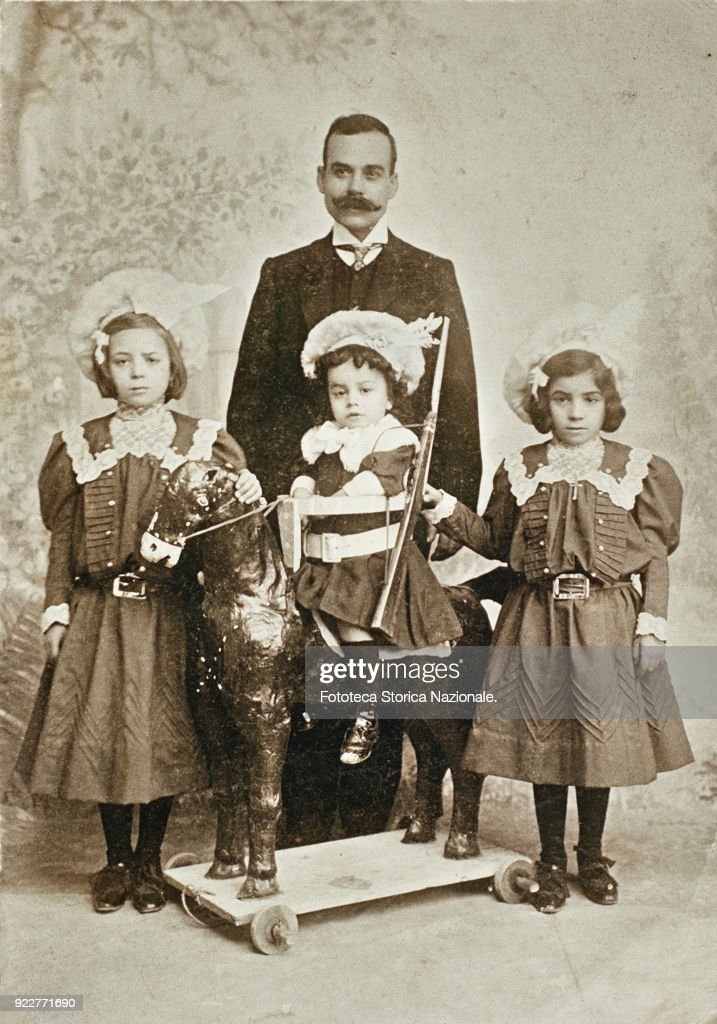 Photography souvenir of a dad with three daughters. At the center the smaller one is sitting on the horse on wheels and her sister help her with a rifle; the backdrop is decorated with trees. Photograph, Italy approx. 1900.