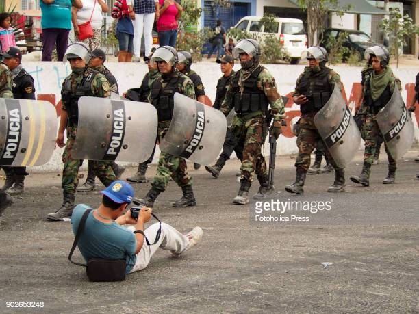 A photojournalist falls to the ground while taking pictures of the police marching to suppress a violent demonstration against public transport...