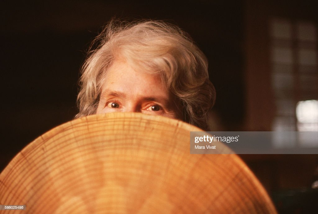 Photojournalist Margaret Bourke-White hides behind a Southeast Asian straw hat.