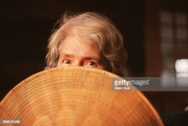 Photojournalist Margaret BourkeWhite hides behind a Southeast Asian straw hat