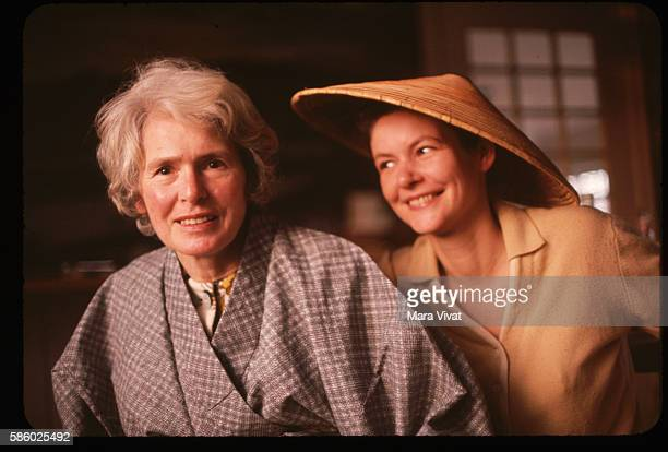 Photojournalist Margaret Bourke-White sits beside a friend wearing a Southeast Asian straw hat.