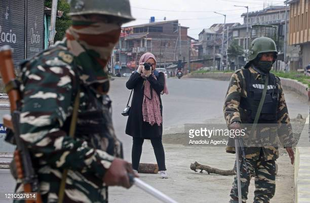 Photojournalist Masrat Zahra takes photos near a temporary checkpoint before going to Cyber Police Station in Srinagar Kashmir on April 21 2020...