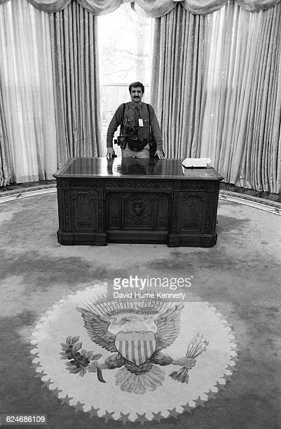 Photojournalist Pete Souza stands behind the new desk in the Oval Office while staff change the furnishings as newly elected Bill Clinton is being...
