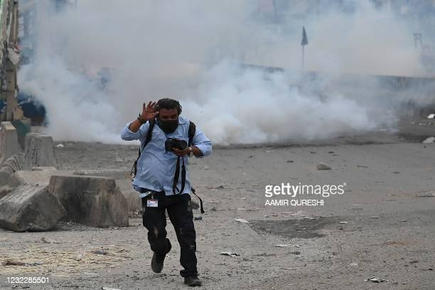 Photo-journalist reacts while riot policemen clash with supporters of Tehreek-e-Labbaik Pakistan party during a protest against the arrest of their...