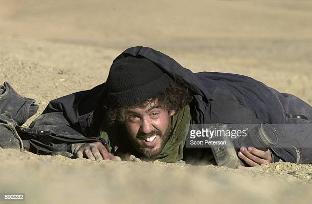 Photojournalist Ron Haviv of the VII agency, reacts to sniper fire from the Northern Alliance during the surrender of the villages of Midan Shar by...