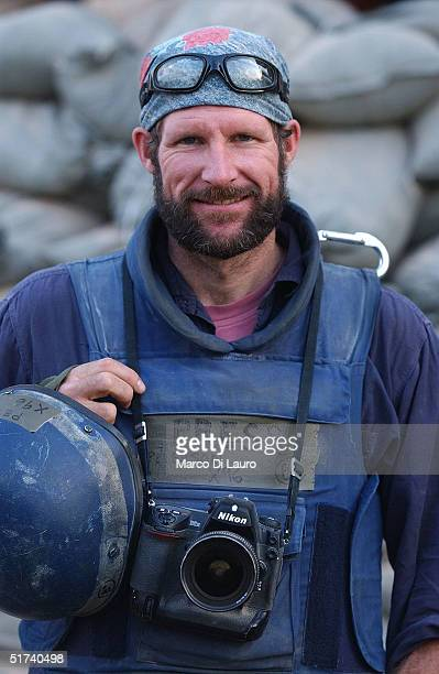 Photojournalist Scott Peterson holds his gear as he covers the US assault on Fallujah November 14 2004 in Iraq Western journalists have no other way...