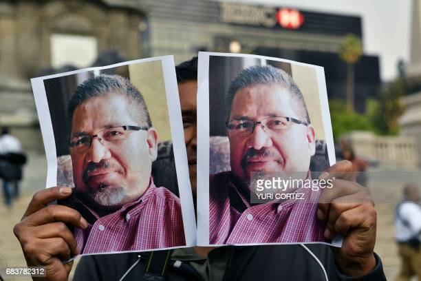 A photojournalist shows pictures of Mexican journalist Javier Valdez murdered on the eve during a protest by journalists in Mexico City on May 16...