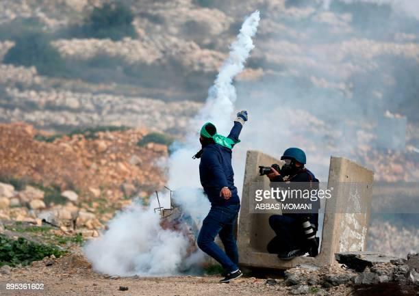 A photojournalist take pictures as a Palestinian protestor throws a tear gas canister back towards Israeli security forces during clashes at Atarot...