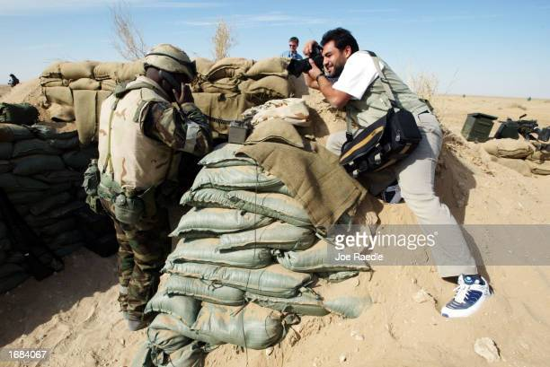 A photojournalist takes a picture of a US Army soldier talking on the field phone during a training exercise December 12 2002 near the Iraqi border...