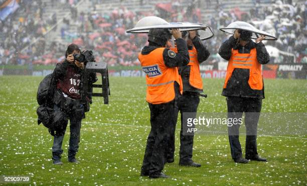 A photojournalist takes a picture of three policeman taking cover under their shields during a heavy rainfall with hail during halftime of the last...