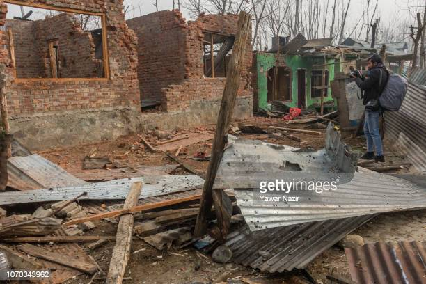 A photojournalist takes pictures of residential houses destroyed in a gun battle between Indian armed forces and militants after a gun battle between...