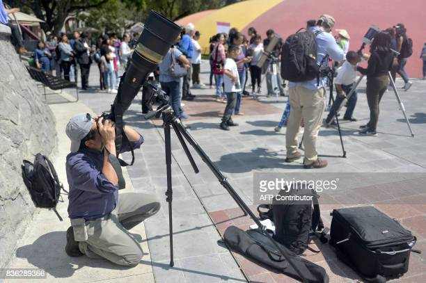 A photojournalist takes pictures of the solar eclipse at the esplanade of the Museum of Natural History in Mexico City on August 21 2017 In Mexico...