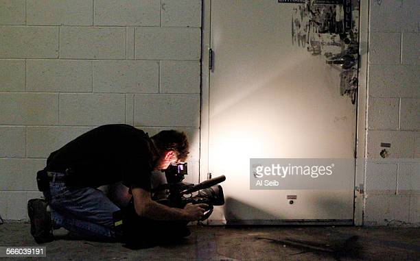 Photojournalist Tom Larson shoots video of the bullet holes at the garage doorway leading to the Adat Yeshurun Shephardic Congregation in North...