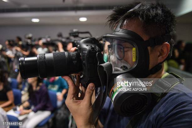 A photojournalist wearing a protective mask attends a police press conference in Hong Kong on October 8 2019 The financial hub has been gripped by...