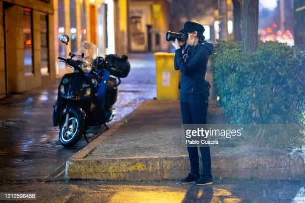 A photojournalist wears face mask and gloves as the country works to stop the spread of the coronavirus on March 15 2020 in Madrid Spain The cases in...