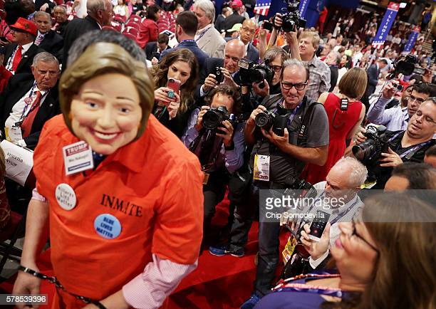 Photojournalists and attendees take pictures of attendee Wes Nakagiri wearing a US Democratic presidential candidate Hillary Clinton mask prior to...
