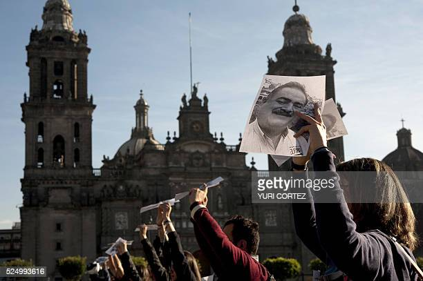 Photojournalists and colleagues of recently murdered editor and founder of El Foro de Taxco newspaper Francisco Pacheco place on the ground pictures...