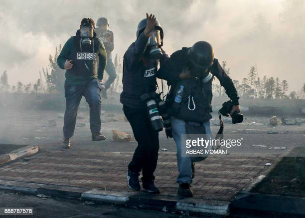 Photojournalists and videojournalists wearing gas masks flee from teargas during clashes with Israeli forces near an Israeli checkpoint in the West...