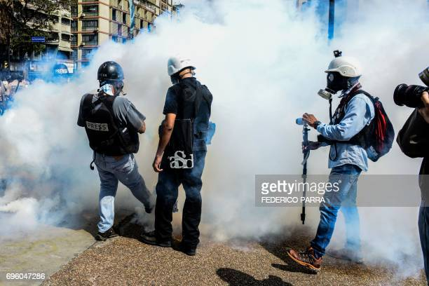 Photojournalists are seen through tear gas thrown by the National Guard to prevent antigovernment demonstrators from gathering at Altamira Square in...