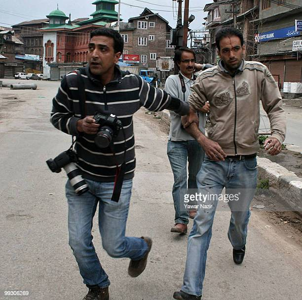 Photojournalists help a wounded civilian after a grenade attack on May 14 2010 in Srinagar Kashmir India Police reports stated that four Indian...