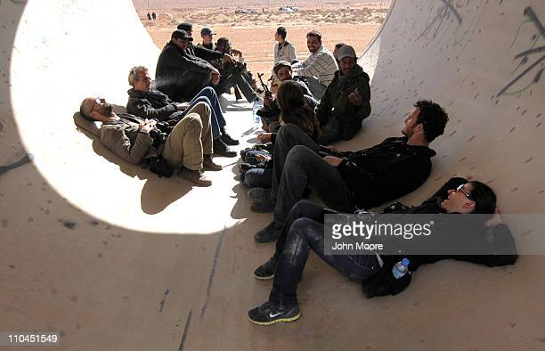 Photojournalists including New York Times photographers Tyler Hicks and Lynsey Addario rest while taking cover in a construction pipe on March 6 2011...