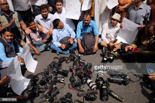 Photojournalists keep down their cameras in protest against Delhi Police's recent assault on media in New Delhi on March 26 2018 Members of the press...